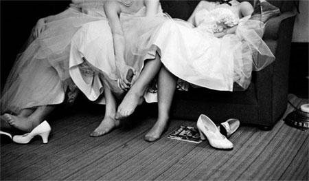 Photo of women in fancy dresses with shoes off, rubbing sore feet